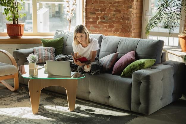 Obteniendo tareas. mujer caucásica, autónoma durante el trabajo en la oficina en casa mientras.