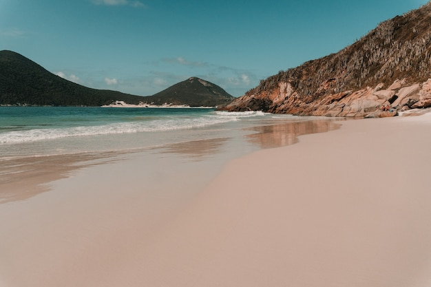 Océano ondulado golpeando la playa de arena rodeada de montañas en río de janeiro.