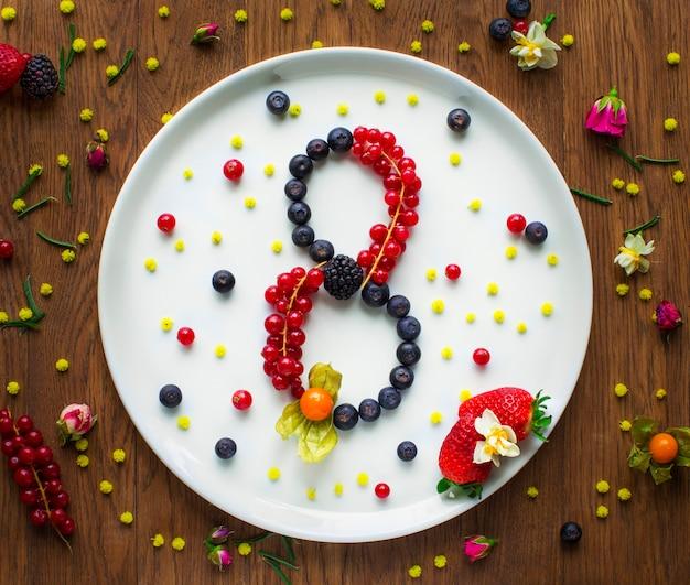 Ocho formas escritas con grosella negra, arándano y balckberry en un plato