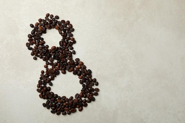 Ocho de granos de café sobre fondo de textura blanca
