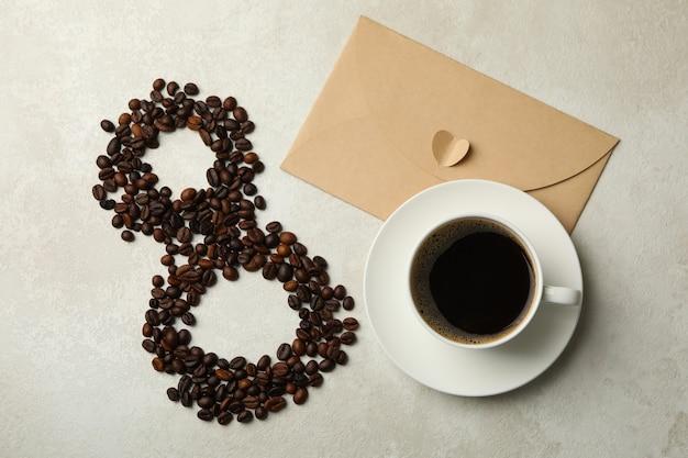 Ocho de granos de café, taza de café y sobre sobre fondo blanco con textura