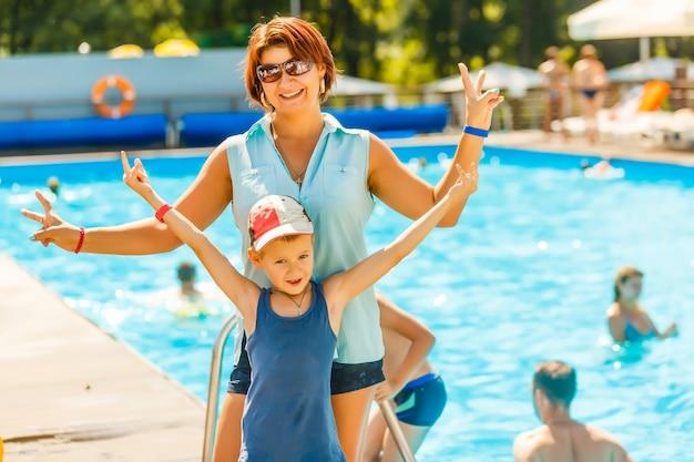 Ocio activo en la piscina, mujer y niño de pie cerca de la piscina sonriendo