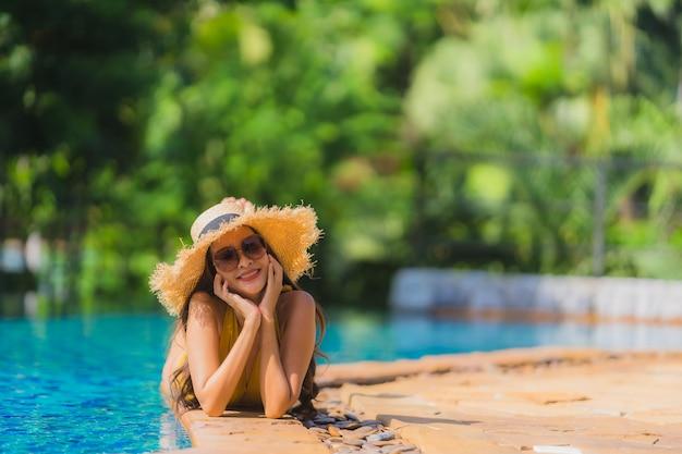 El ocio asiático joven hermoso de la mujer del retrato relaja sonrisa y feliz alrededor de piscina en centro turístico del hotel
