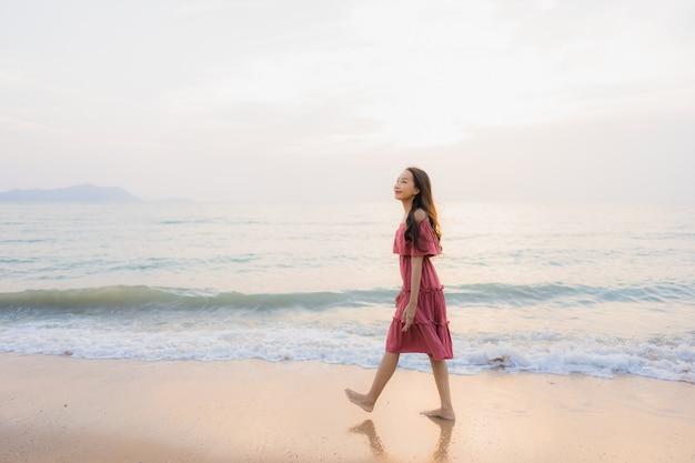 Ocio feliz de la sonrisa de la mujer asiática joven hermosa del retrato en el mar y el océano de la playa
