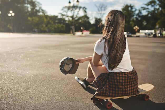 Ocio, hobby y skate en el concepto de ciudad. vista trasera, adolescente
