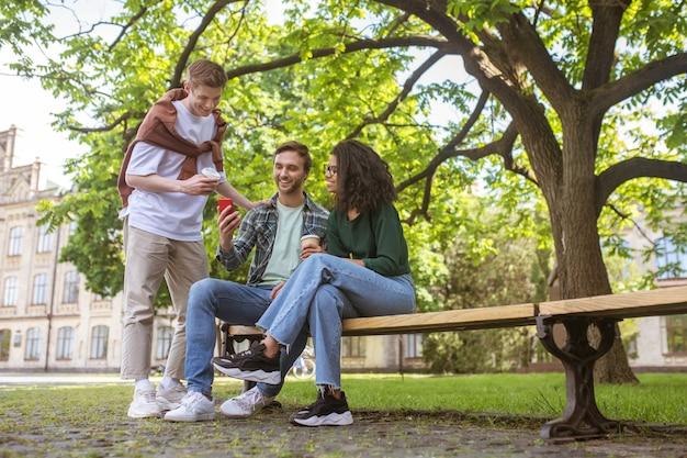 Ocio. tres amigos pasando tiempo en el parque y hablando.