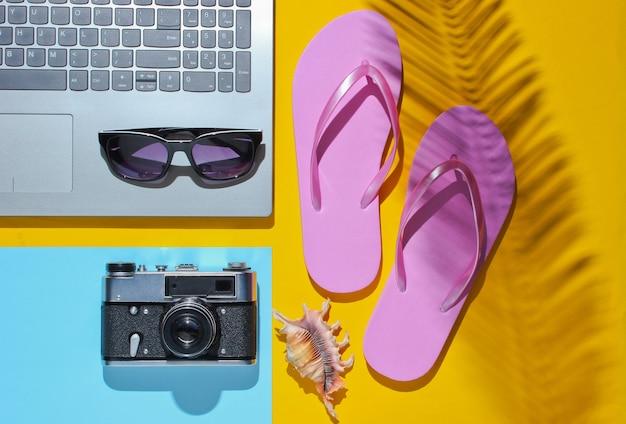 Ocio de verano. el verano relájese. accesorios para portátil y playa sobre un fondo azul amarillo con sombra de hoja de palma.