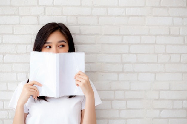 La ocultación feliz de la mujer asiática hermosa del retrato detrás abre el libro