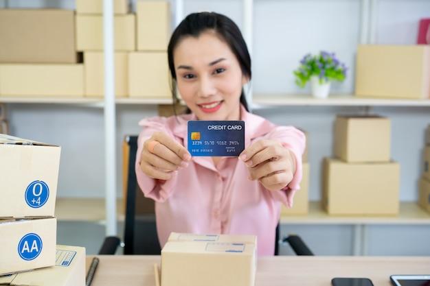 Ocupada joven asiática, que es vendedor en línea, mostrando una tarjeta de crédito