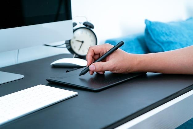 El ocupado diseñador gráfico que trabaja en la computadora con un lápiz digital.