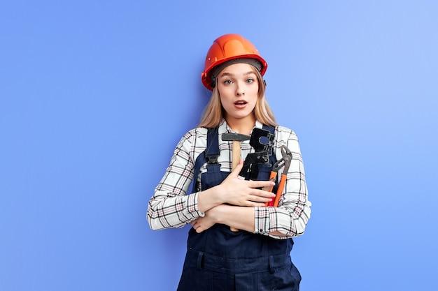 Ocupado ingeniero constructor mujer mirando a cámara con expresión de sorpresa sosteniendo en la mano herramientas ajustables
