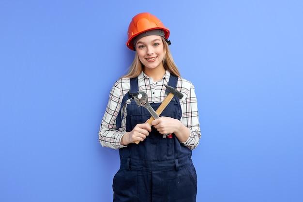 Ocupado ingeniero constructor mujer mirando a cámara sosteniendo en la mano herramientas ajustables