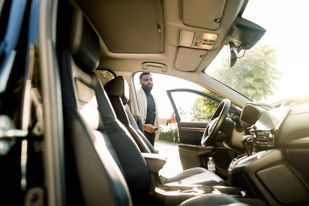 Ocupado joven africano en traje en coche. hombre de negocios joven feliz que consigue dentro de su coche. hombre africano en traje caminando en su vehículo.