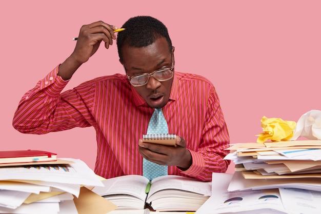 Ocupado, de piel oscura, mira fijamente el cuaderno de espiral, desconcertado con la lista de tareas pendientes, tiene mucho trabajo antes de dar una conferencia para los estudiantes, se rasca la cabeza con un lápiz