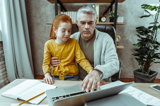 Ocupado con trabajo. agradable hombre serio sosteniendo a su hija mientras presiona el botón de su computadora portátil