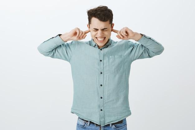 Odio cuando los padres discuten en voz alta. retrato de hombre caucásico enojado incómodo en traje casual