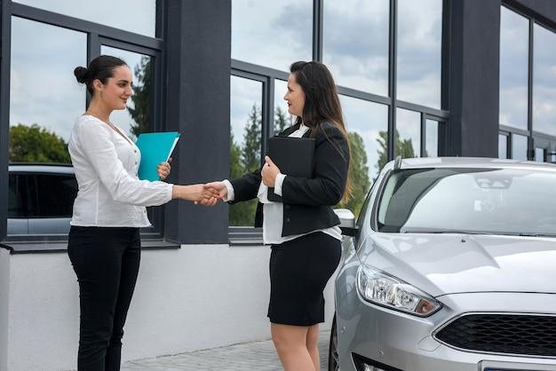 Oferta de compra de coche. dos hermosas mujeres apretón de manos cerca de coche nuevo parado afuera y sonriendo