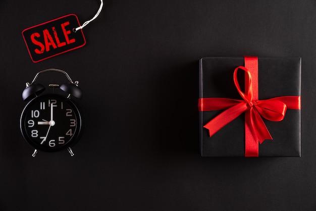 Oferta de viernes negro con caja de regalo negra y reloj despertador