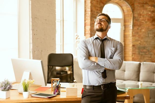 Ofertas. un joven empresario que trabaja en la oficina, consiguiendo un nuevo lugar de trabajo. oficinista de sexo masculino joven mientras gestiona después de la promoción. parece serio, confiado. negocio, estilo de vida, concepto de nueva vida.
