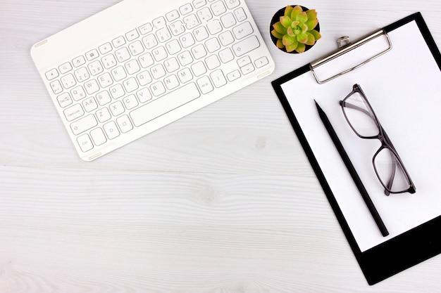 Office flatlay con teclado blanco, gafas de lectura, mascota y cuaderno