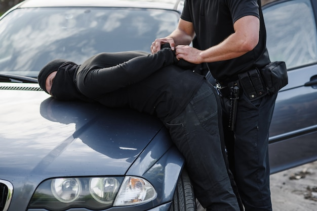 Un oficial de policía arrestó al delincuente con una máscara con un automóvil robado y lo esposó en el capó del automóvil.