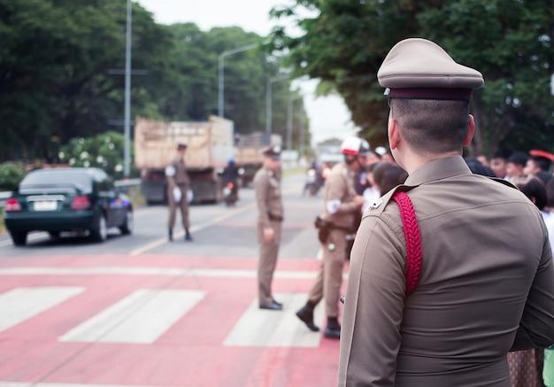 El oficial de policía ayuda y sirve a las personas en el camino