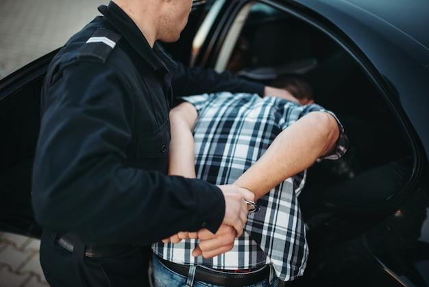 El oficial de policía metió al intruso en el auto.