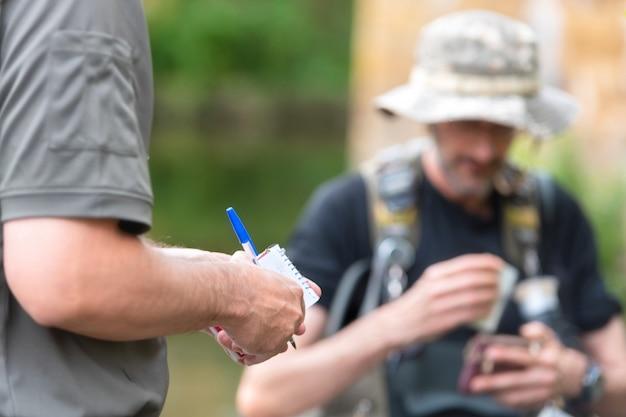Oficial de policía o guardabosques que comprueba la licencia de pescador en el río. inspección de pesca. ley.