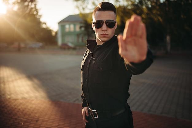 Oficial de policía serio muestra una señal de stop de mano