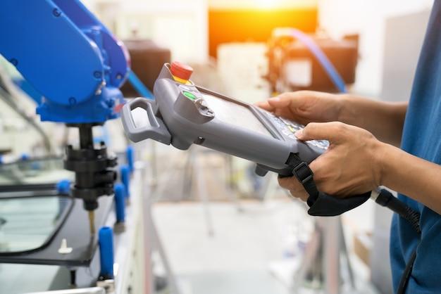 El oficial profesional le enseña el robot usando el panel de control al cristal en la base de la plantilla