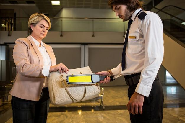 Oficial de seguridad del aeropuerto con un detector de metales para registrar una maleta