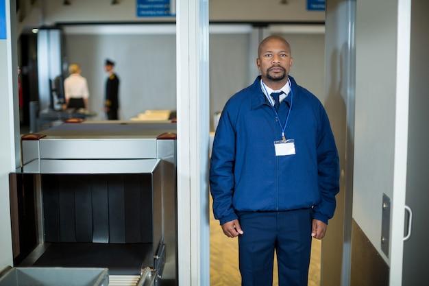 Oficial de seguridad del aeropuerto de pie en la puerta del detector de metales