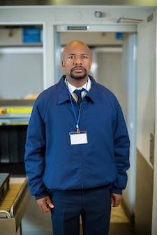 Oficial de seguridad del aeropuerto de pie en la terminal del aeropuerto