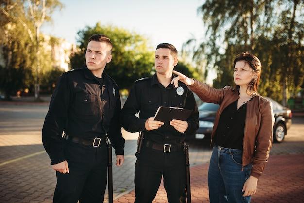 Oficiales de policía que escuchan el testimonio del conductor