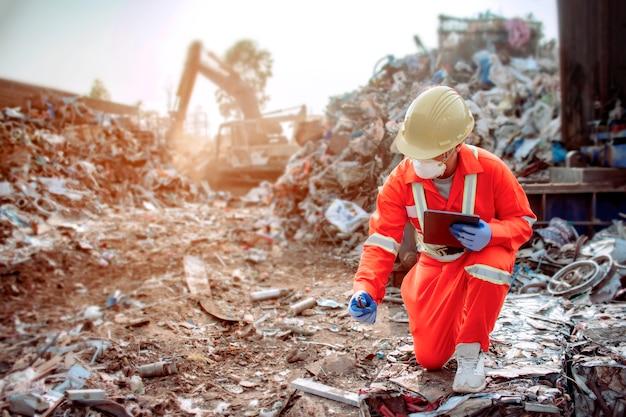 Oficiales que visten bien y cumplen con los estándares de trabajo inspección de desechos grandes para clasificar antes de ser reciclados