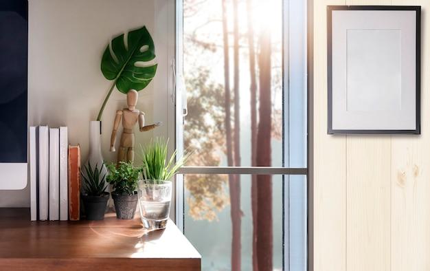 Oficina en casa con computadora de escritorio, libros y planta de interior.