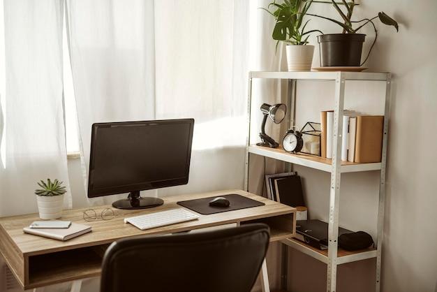 Oficina en casa con computadora y estante
