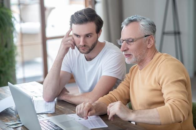 Oficina en casa. dos hombres sentados nat la mesa y trabajando en una computadora portátil