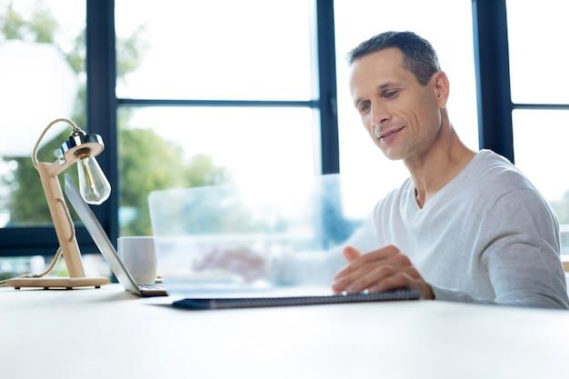 En la oficina. encantado de apuesto hombre de negocios inteligente sonriendo y abriendo una carpeta con documentos mientras está en el trabajo