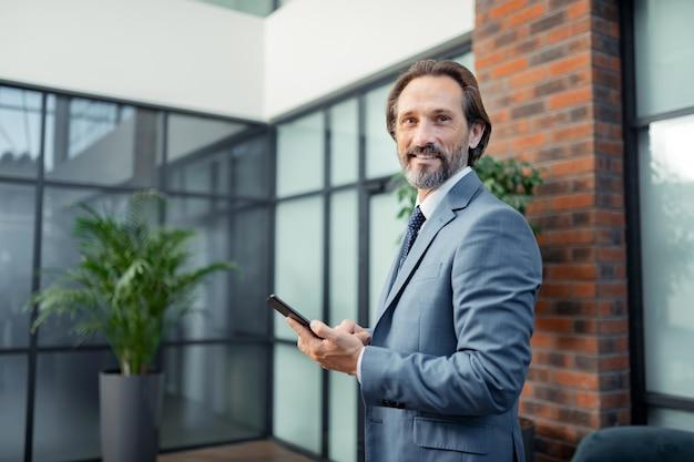 Oficina espaciosa y moderna. hombre de negocios guapo con barba de pie en su moderna y espaciosa oficina