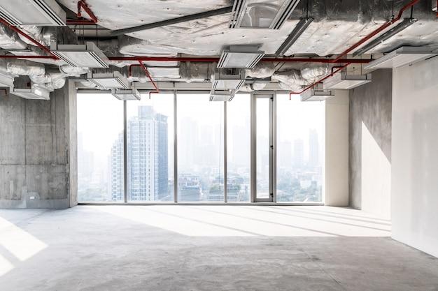 Oficina de gran altura en construcción con techo abierto para ver la estructura y el funcionamiento del sistema, ventanas de vidrio para tomar una vista aérea de los edificios de la ciudad. espacio vacío para la inversión del desarrollador.