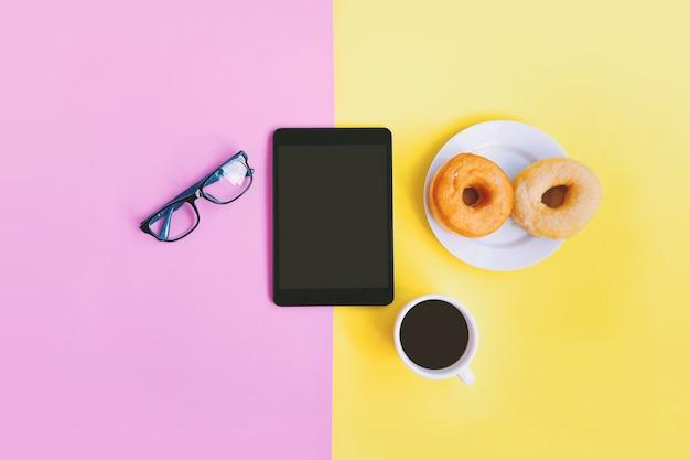 Oficina en el hogar, café, donuts, anteojos y tableta en fondo pastel con espacio de copia