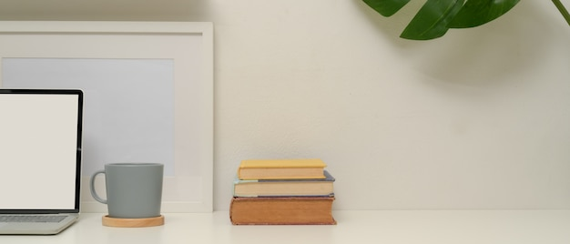 Oficina en el hogar mínima con maqueta portátil, taza, libros, marco, casa de planta y espacio de copia en mesa blanca