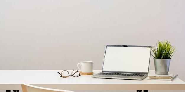 Oficina en el hogar simple con computadora portátil con pantalla en blanco abierta