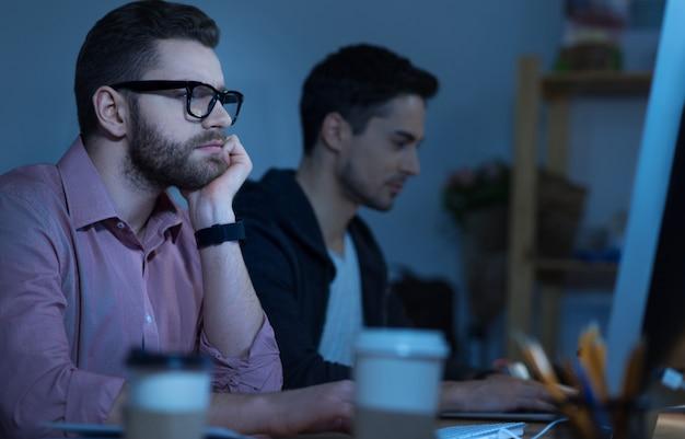 En la oficina. hombre agradable pensativo guapo sentado en la mesa y sosteniendo su barbilla mientras trabaja en la computadora