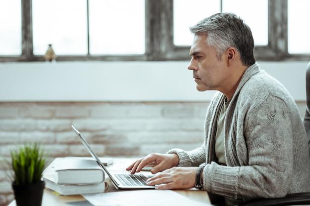 En la oficina. hombre inteligente serio escribiendo en el teclado mientras está en el trabajo