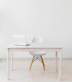 Oficina minimalista con mesa y portátil.
