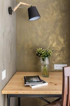 Oficina moderna un escritorio y una silla al lado. la pared está cubierta de yeso decorativo verde, un jarrón con flores y revistas sobre la mesa
