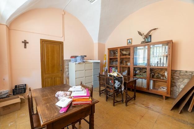 Oficina con muebles clásicos y símbolos católicos.