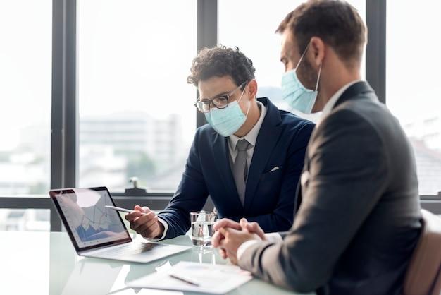 Oficina en nueva normalidad, hombres con máscara médica covid 19